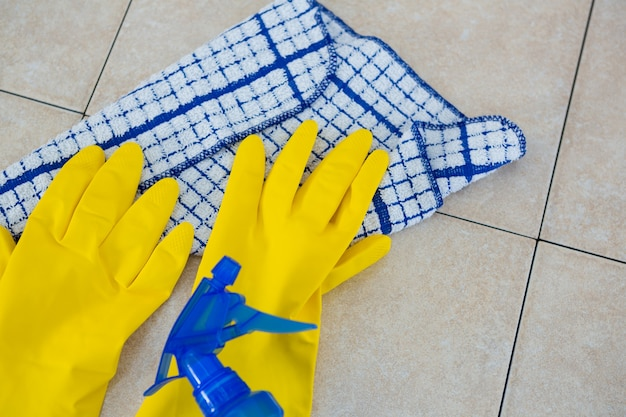 Overhead view of gloves with napkin and spry on floor