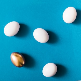 Overhead view of golden egg among the white eggs on blue background