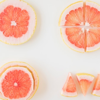 An overhead view of grapefruit cut in different shape and slice over the white backdrop