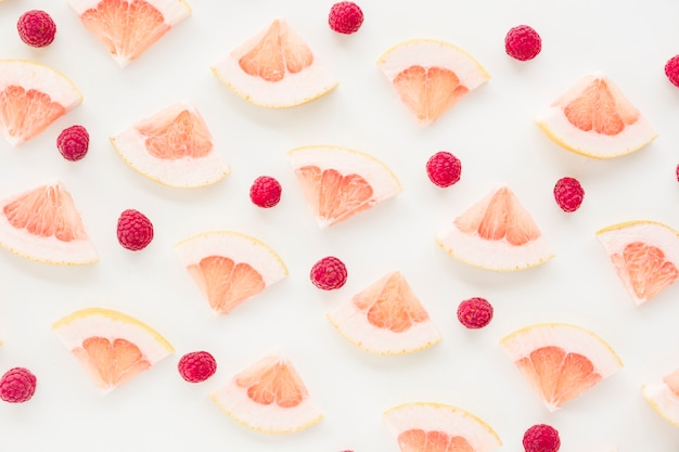 An overhead view of grapefruit slice and raspberries on white background