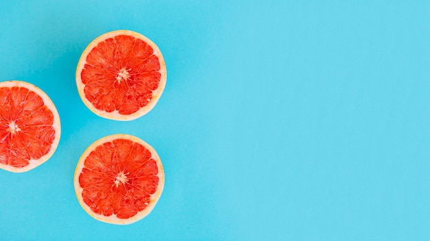 Overhead view of grapefruit slices on blue background