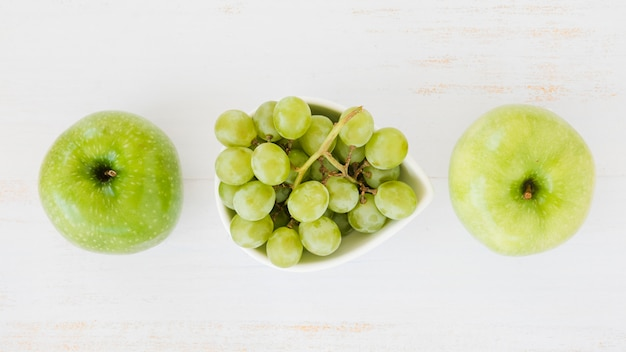 An overhead view of green apples with grapes on white wooden textured backdrop