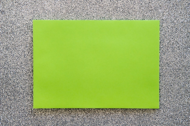 Overhead view of green cardboard paper on grey backdrop