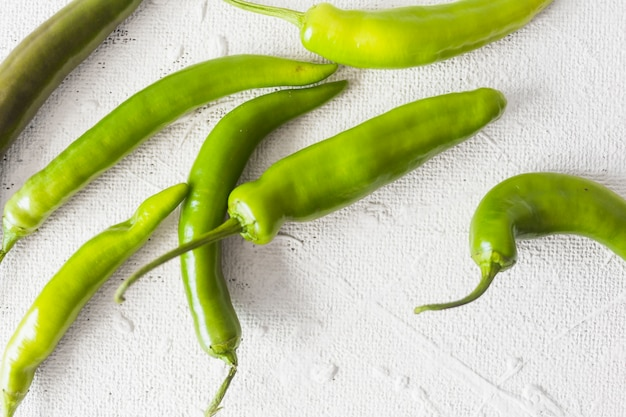 An overhead view of green chilies on texture backdrop