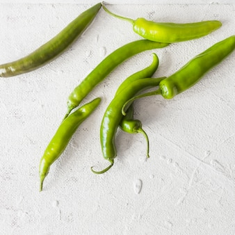 An overhead view of green chilies on white texture backdrop