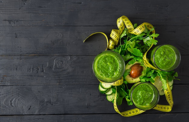 Overhead view green detox smoothie with measuring tape