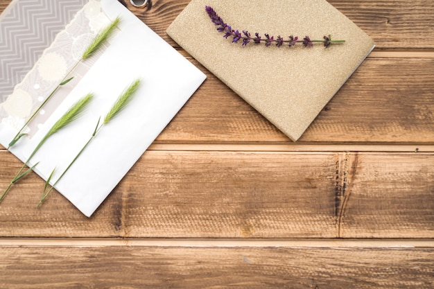 Overhead view of green ears of wheat on greeting card and lavender twig on wooden table