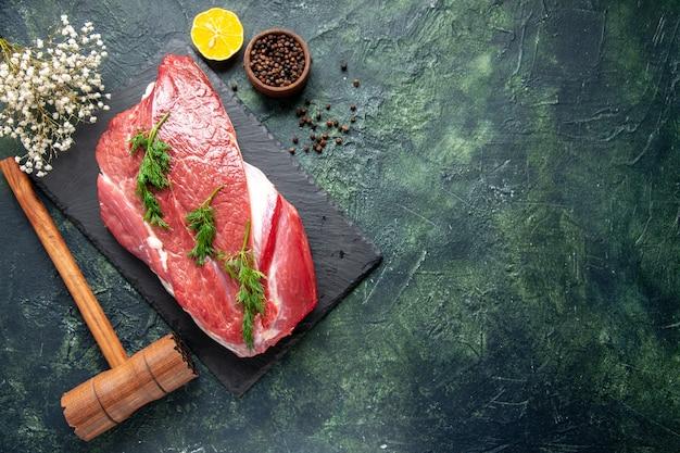 Vista dall'alto di verde su posate di carne cruda rossa fresca su tagliere e martello di legno di limone pepe su sfondo nero verde mix di colore