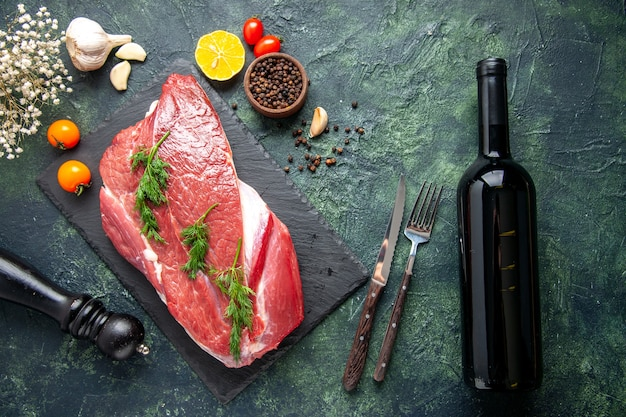 Vista dall'alto del verde su carne cruda rossa fresca su tagliere e pepe limone nero martello fiore bottiglia di vino su sfondo nero verde mix di colore
