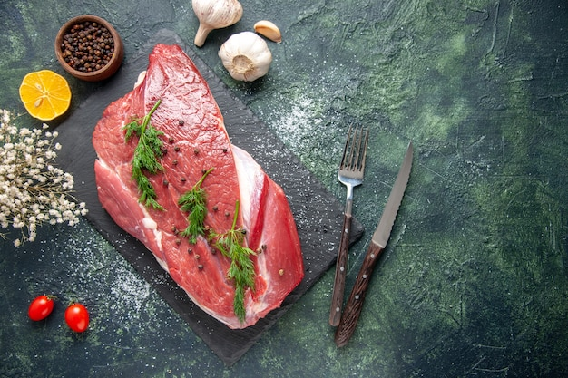 Vista dall'alto di verde su carne cruda rossa fresca su tagliere e fiore di limone pepe su sfondo di colore verde misto nero