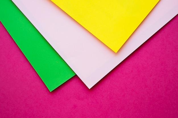 Vista dall'alto del verde; carte di cartone grigio e giallo su superficie rosa