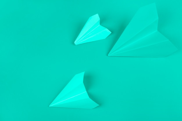 An overhead view of green paper airplanes on mint background