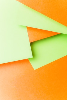 An overhead view of green paper over the orange backdrop