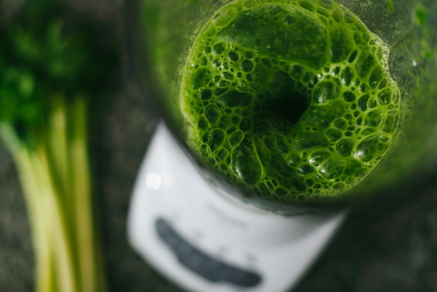 Overhead view of green smoothie in blender