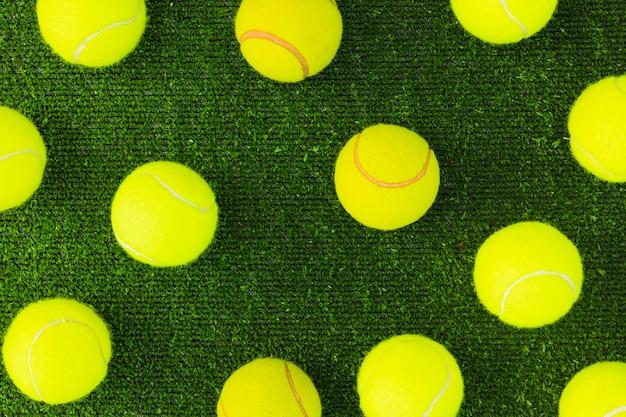 An overhead view of green tennis balls on turf