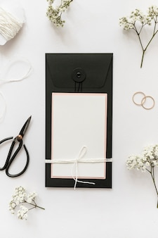 An overhead view of greeting cards with scissor; wedding rings; string and flower on white background