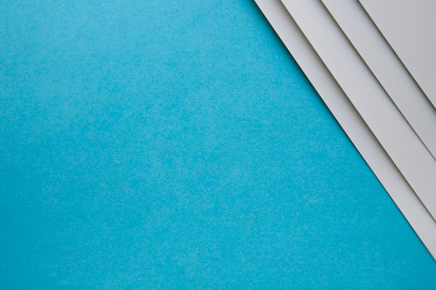 Overhead view of grey cardboard papers on blue backdrop