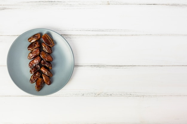 An overhead view of grey plate with arranged juicy dates on white wooden desk