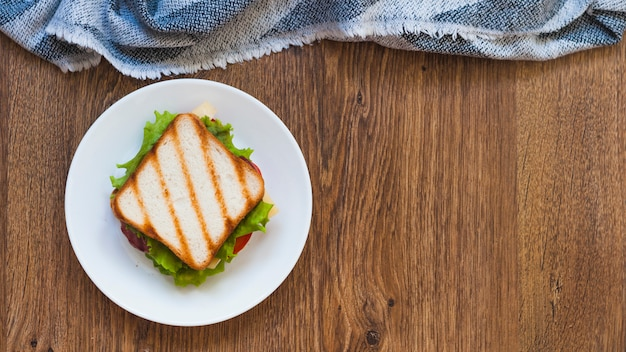 An overhead view of grilled sandwich on white plate with napkin