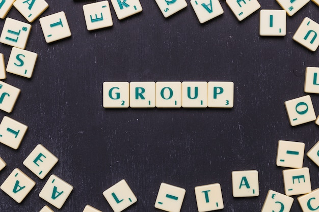 Overhead view of group text on scrabble letters over black backdrop