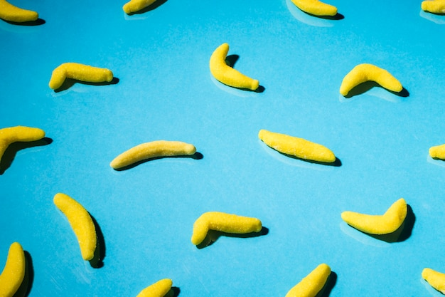 Overhead view of gummy banana candies on blue backdrop