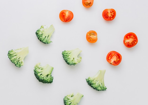 An overhead view of halved cherry tomatoes and broccoli on white backdrop