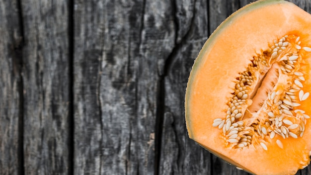 An overhead view of halved musk melon on an old wooden backdrop