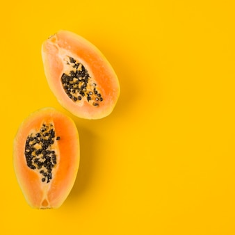 An overhead view of halved papaya with seeds on yellow backdrop