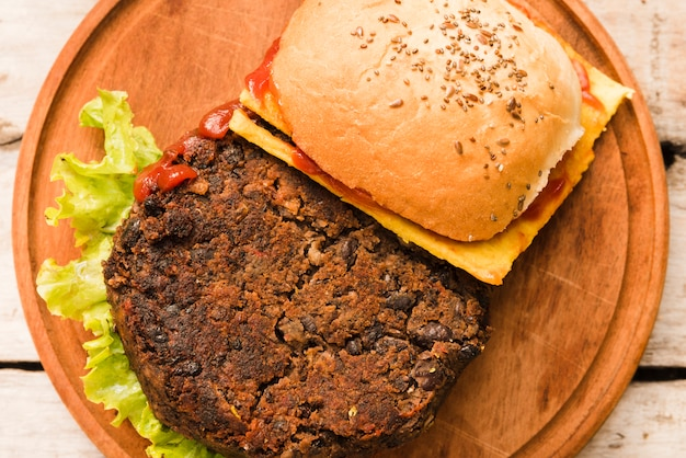 An overhead view of hamburger with cheese; tomatoes and lettuce on wooden chopping board