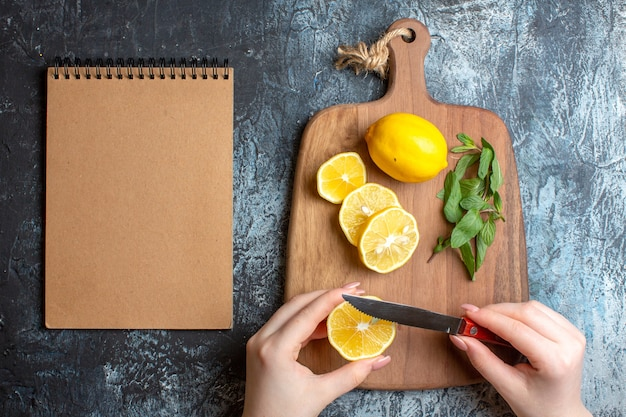 Overhead view of a hand chopping fresh lemons and mint on a wooden cutting board next to spiral notebook on dark background