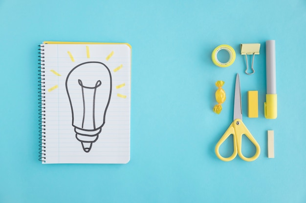 Overhead view of hand drawn light bulb on notebook with stationary on blue background