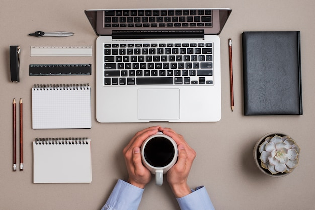An overhead view of hand holding coffee cup with office supplies and laptop on colored desk