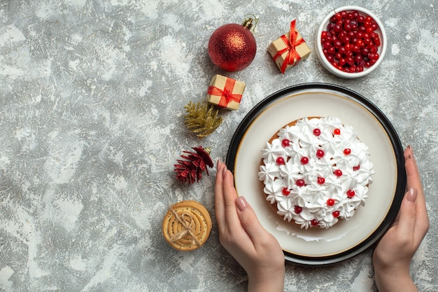 Overhead view of hand holding delicious cake with cream currant on a plate and gift boxes stacked cookies conifer cones on gray background
