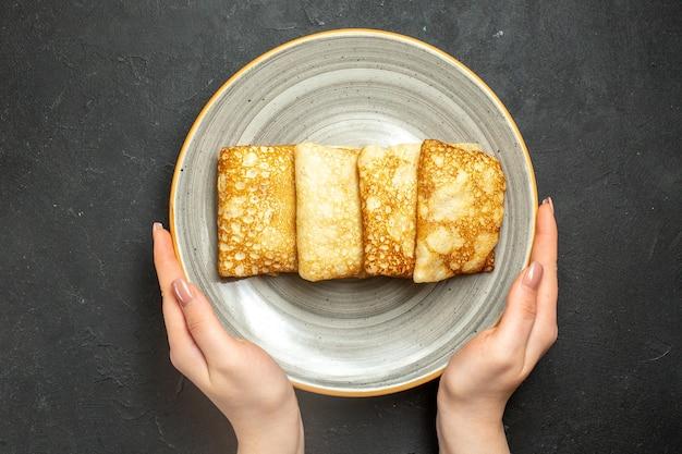 Vista dall'alto della mano che tiene deliziosi pancake ripieni di carne su un piatto bianco su sfondo nero