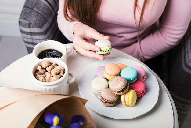 An overhead view of hand holding macaroon with brown sugar cubes and coffee cup on white table