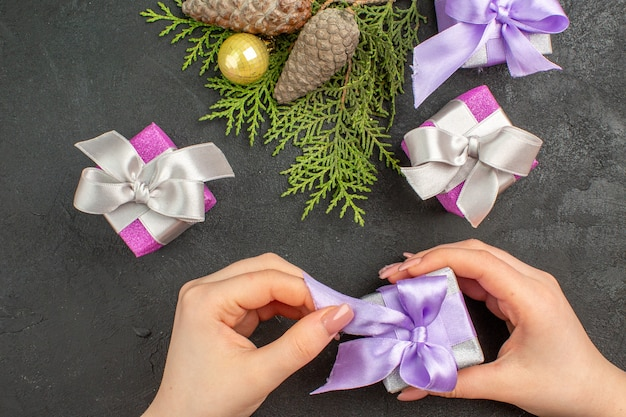 Overhead view of hand holding one of colorful gifts and decoration accessories on dark background
