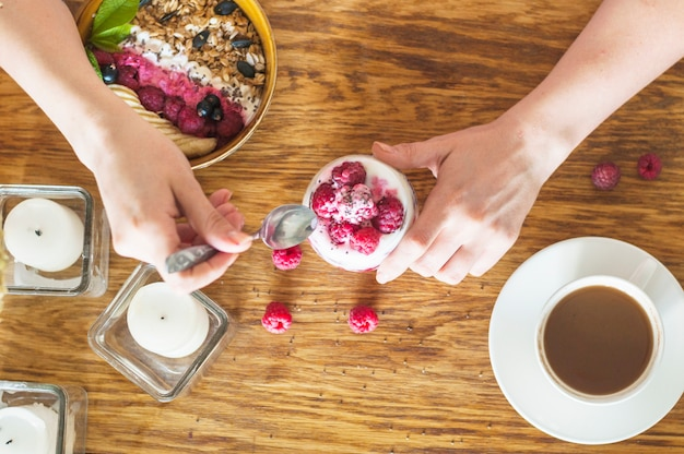 An overhead view of hand holding spoon and glass of yogurt with raspberries on wooden table
