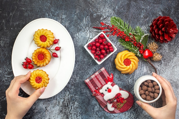 Vista dall'alto della mano prendendo deliziosi biscotti decorazione accessorio calza di babbo natale e cornell in una ciotola rami di abete sulla superficie scura