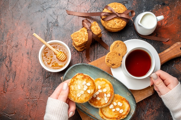 Overhead view of hand taking tray with fresh pancakes a cup of black tea on a wooden cutting board honey stacked cookies milk on a dark surface