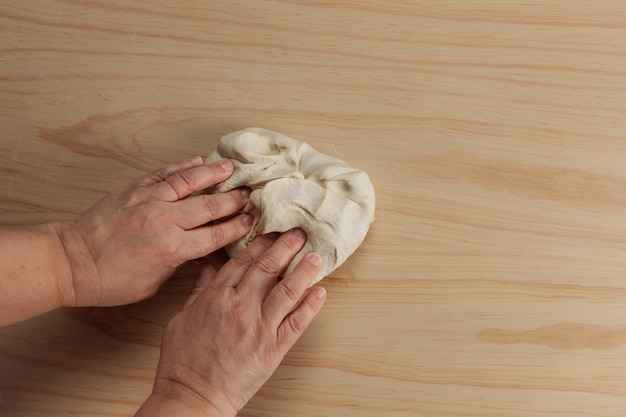 Overhead view of the hands of an adult woman kneading pizza dough in a wooden table in the kitchen