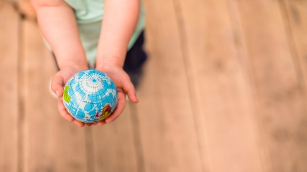 An overhead view of hands holding globe ball against hardwood floor