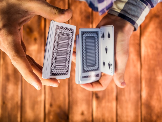 Overhead view of hands mixing playing cards on the wooden surface