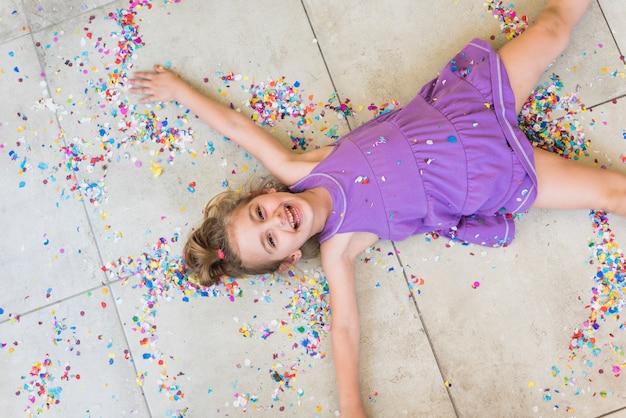Punto di vista ambientale della ragazza sveglia felice che si trova con i coriandoli sul pavimento