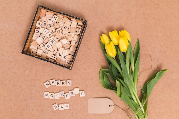 Overhead view of happy mother's day text; yellow tulip flowers; price tag and wooden blocks over brown backdrop