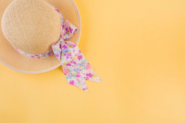 An overhead view of hat with floral ribbon bow on yellow backdrop