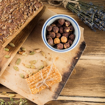 An overhead view of hazelnut bowl with bread and sesame bar on chopping board