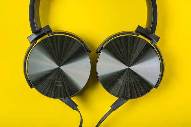 An overhead view of headphone on yellow backdrop