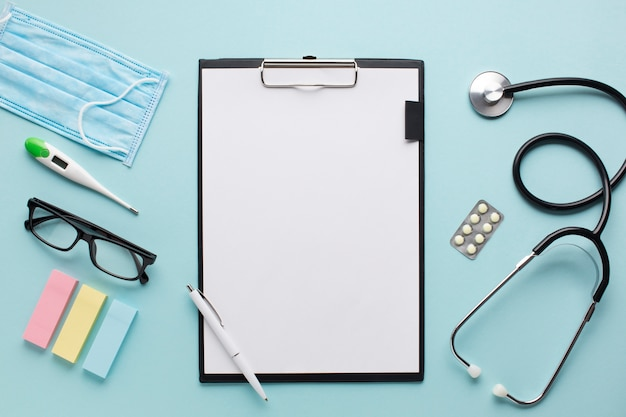 Overhead view healthcare accessories near clipboard with plank paper and spectacles on background