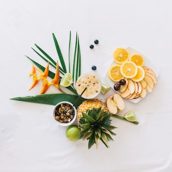 An overhead view of healthy breakfast with bird of paradise flower on white backdrop