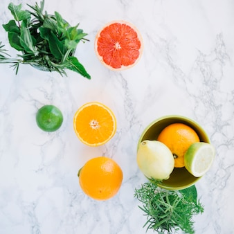 Overhead view of healthy citrus fruits and rosemary on marble